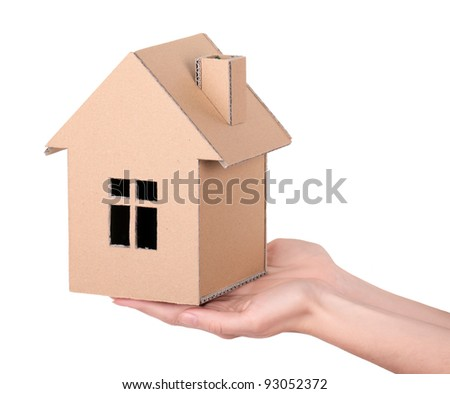 Hands hold a toy house, made of cardboard, isolated on white background