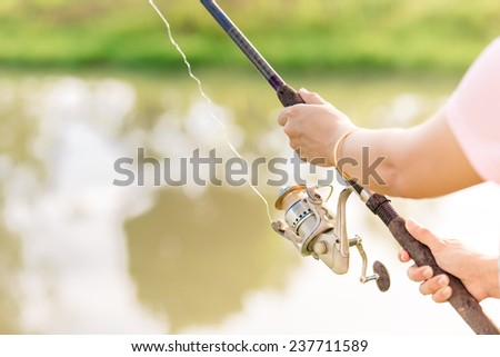 Hands hold fishing reel at pond - stock photo