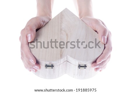 Hands hold heart shaped wooden gift box isolated on white - stock photo