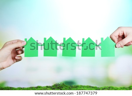 Hands hold houses on grass on natural background
