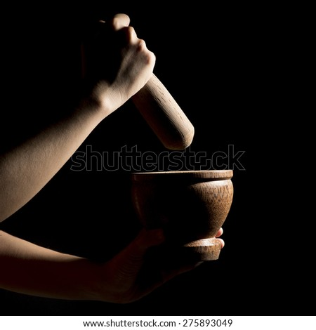 hands hold pestle and crush to the wooden mortar on black background - stock photo
