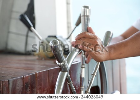 Hands hold steering wheel the boat - stock photo