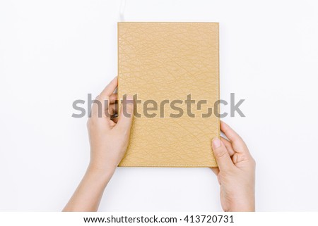 Hands hold the book on white background - stock photo
