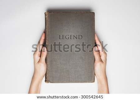 "hands hold the  book with a word of "" Legend "" on cover - stock photo"