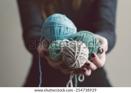 Hands holding a balls of yarn - stock photo