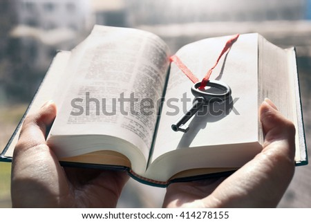 Hands holding a book with vintage key in it. Close up - stock photo