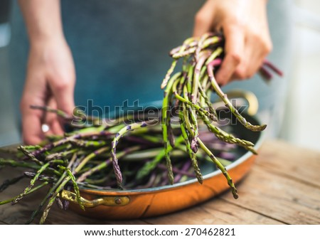 Hands holding a bunch of fresh asparagus. Selected focus and shallow DOF - stock photo