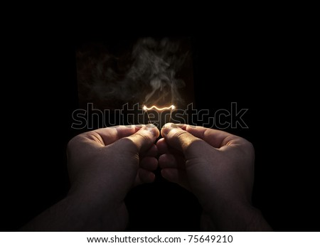 hands holding a burning filament - stock photo
