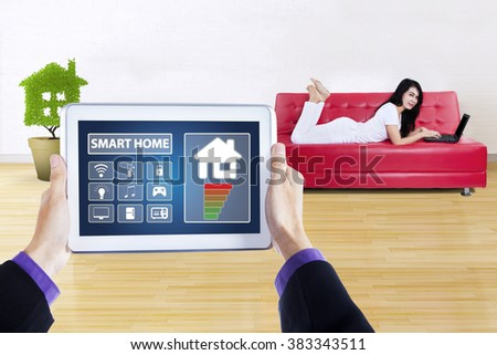 Hands holding a controller of smart home system on the digital tablet, shot with pretty woman using laptop on the couch - stock photo