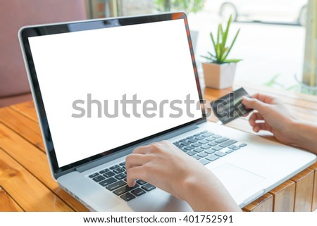 Hands holding a credit card and using laptop computer for online shopping - stock photo