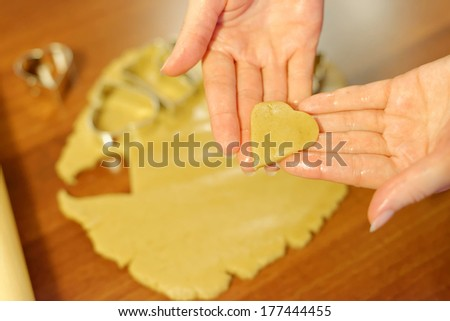 Hands holding a cutout of cookie dough in the shape of a heart.