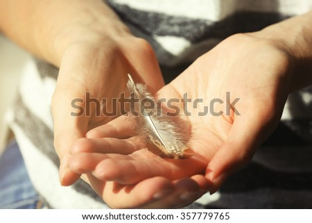Hands holding a feather, close-up
