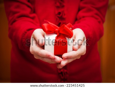 Hands holding a gift with red bow - stock photo