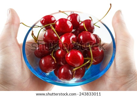 Hands holding a glass bowl with fresh cherry fruits  - stock photo