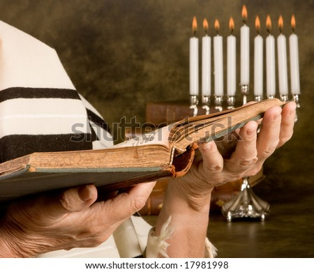 Hands holding a jewish prayer book wearing a prayer shawl - stock photo