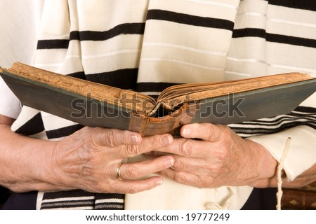 Hands holding a jewish prayer book wearing a prayer shawl - stock photo
