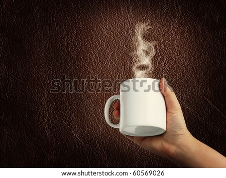 Hands holding a mug against a textured background - stock photo
