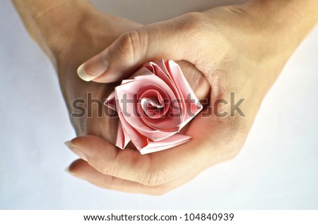 Hands holding a pink paper rose - stock photo