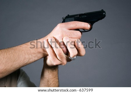 Hands holding a pistol on fighting position - stock photo