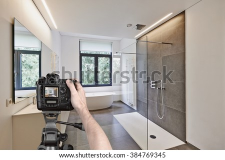 Hands holding a professional camera on tripod taking picture in  tiled bathroom with windows towards garden - stock photo