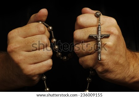 Hands holding a rosary - stock photo