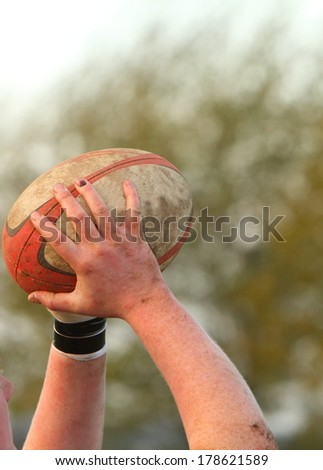 Hands holding a rugby ball - stock photo