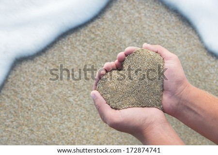 Hands holding a sand in form of the heart - honeymoon at beach concept - stock photo