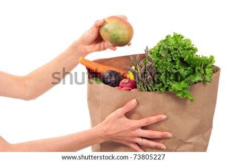 Hands holding a shopping paper bag full of groceries, one hand taking out ripe mango, avocado, asparagus, carrots, radish, lime and lemon on a white background - stock photo