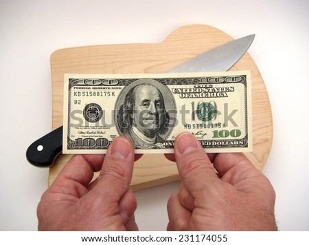 Hands Holding A Single United States One Hundred Dollar Federal Reserve Note Above A Chef's Knife Resting On The Surface Of A Bread Shaped Cutting Board Over A White Surface With Slight Vignetting. - stock photo