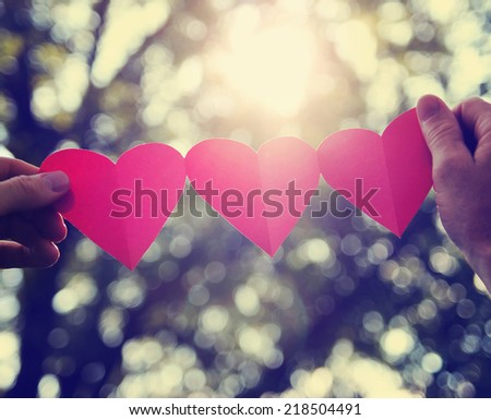 hands holding a string of paper hearts up to the sun during sunset toned with a retro vintage instagram filter effect  - stock photo