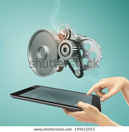 hands holding a tablet with metal gears and cogs wheels - stock photo