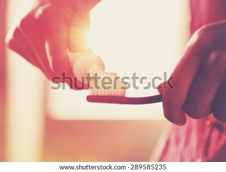 Hands holding a toothbrush and placing toothpaste on it in morning sunrise - stock photo