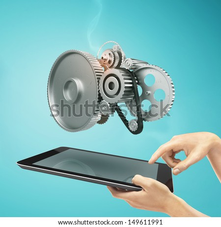 hands holding a  touch pad with metal gears and cogs wheels - stock photo