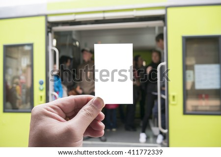 Hands holding a white business card, close up on blurred of train station. Copy space, selective focus, vintage color - stock photo