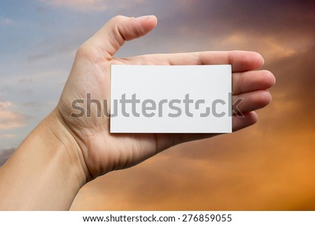 Hands holding a white business visit card, gift, ticket, pass, present closeup on sky background. Copy space - stock photo