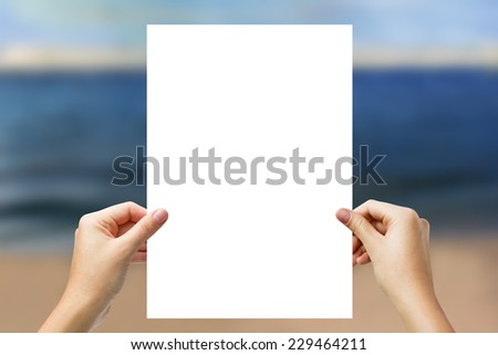 Hands holding a white paper blank isolated on beach background  - stock photo