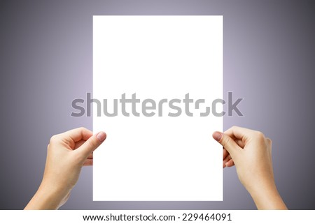 Hands holding a white paper blank isolated on light purple background  - stock photo