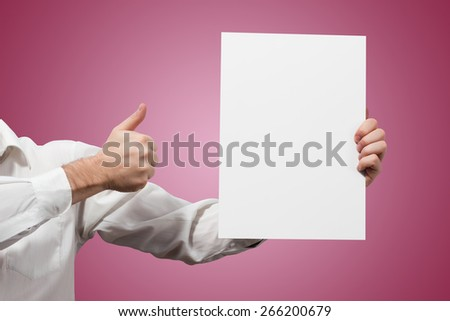 Hands holding a white paper blank isolated on pink background - stock photo