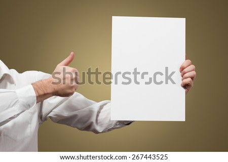 Hands holding a white paper blank placard billboard poster isolated on brown background - stock photo