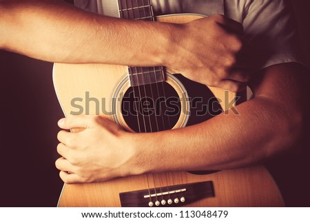 hands holding an acoustic guitar - stock photo