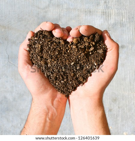 Hands holding an earth heart - stock photo