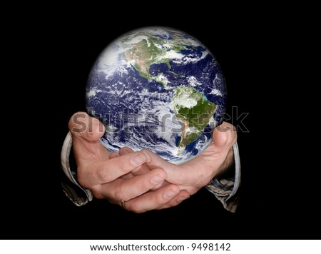 Hands holding an earth planet against a black isolated background - stock photo