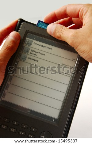 hands holding an electronic book and inserting in it a memory card