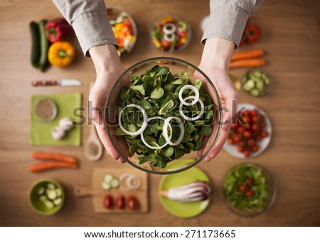 Hands holding an healthy fresh vegetarian salad in a bowl, fresh raw vegetables on background, top view - stock photo
