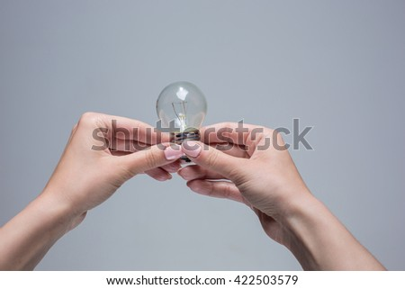 Hands holding an incandescent light bulb on gray background - stock photo