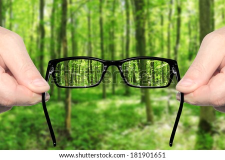 Hands holding and offering eye glasses to look at amazing green forest landndscape.Sharp as a good sight symbol and unsharp as a bad sight symbol  - stock photo