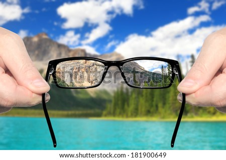 Hands holding and offering eye glasses to look at amazing mountain lake landscape.Sharp as a good sight symbol and unsharp as a bad sight symbol  - stock photo