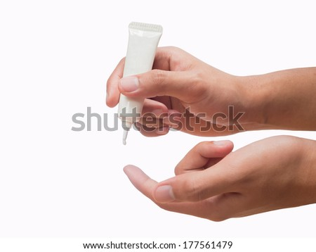 Hands holding and squeezing tube of cream or gel  isolated - stock photo