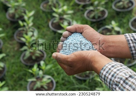 hands holding artificial fertilizer  - stock photo