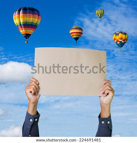 Hands holding banner with hot air balloon and blue sky background - stock photo